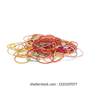 Rubber bands randomly scattered on a white surface.