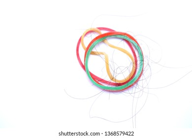 Rubber bands of various colors, with hair stuck on a white background.