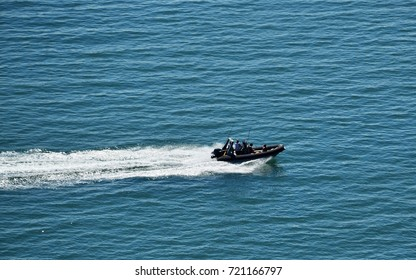 Rubber boat crossing the blue sea water and left white line behind it