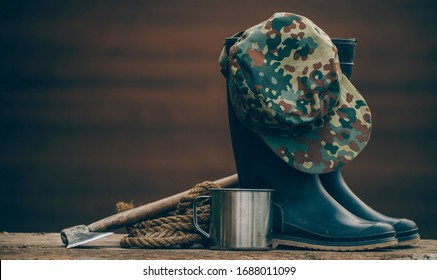Rubber boots camouflage cap, metal mug for camping posing on a wooden background