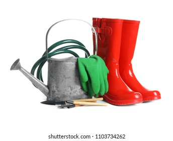 Rubber boots and gardening tools on white background