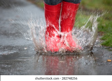 Rubber boots are jumping into a big puddle with splash.