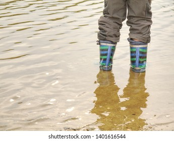 Rubber boots in the muddy water puddle, wavy water level. Advertising of footwear. Baby boots.