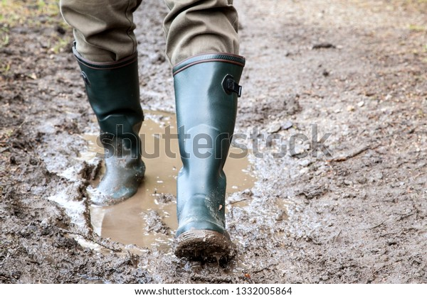 With rubber boots on the way on dirty paths. A hunter goes with his rubber boots on a muddy path through his hunting area.