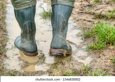 With rubber boots through the mud. Farmer goes with his rubber boots in the muddy lane of his tractor across the field. View from behind.