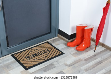 Rubber boots, umbrella and mat near door in hallway