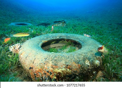 Rubber car tyres pollution on ocean coral reef. Plastic pollutes sea