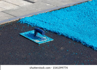 Rubber coating for playgrounds applied on the surface by a steel trowel. PDM rubber granules. Floor covering for sports. Rubber mulch for safety and injury prevention. Selective focus.