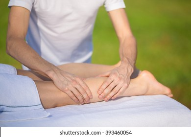 Rubber is doing massage of gastrocnemius muscle to young girl outside.
