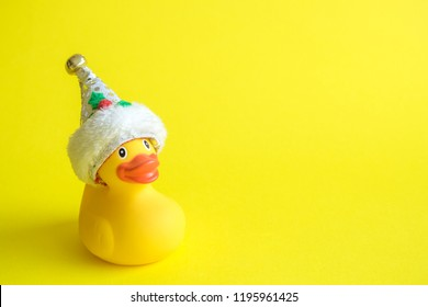 Rubber duck with Santa hat on yellow background minimal creative concept. Space for copy.
