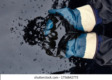 Rubber gloves soaked in oil on the background of spilled oil. Crisis of the oil industry. Economic downturn. Black gold.