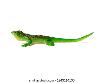 Rubber green iguana toy on white background.