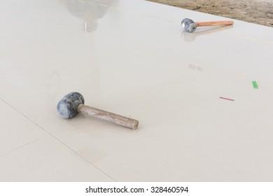 Rubber hammer on floor tile installation for house building