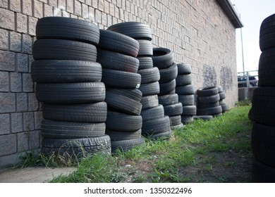 Rubber Industry Stacked Used Tires Against Brick Wall