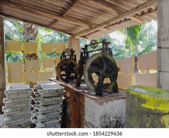 Rubber pressing machinery with latex trays in a small production house at a Rubber Plantation in India