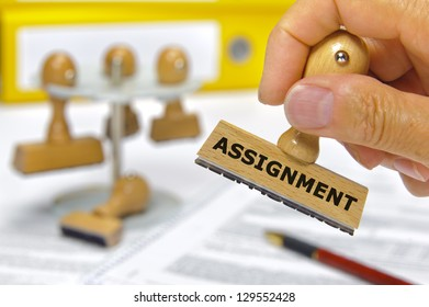 rubber stamp in hand marked with assignment