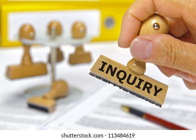 rubber stamp in hand marked with inquiry