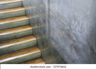 Rubber wood top stairway and modern loft style gray concrete wall. Concept for interior design and architecture.