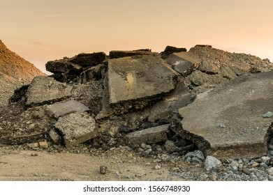 Rubble on a road construction site, broken asphalt and pieces of bitumen layer of a road surface from the demolition of a road in the sunset