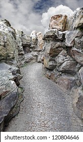 A rubble road through a rocky chasm against a dramatic blue cloudy sky.
