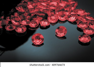 Rubies scattered on a shiny surface with prominent ruby in the middle