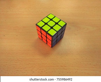 Rubik's Cube on a wooden background. Rubik's Cube invented by a Hungarian architect Erno Rubik in 1974.