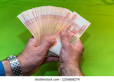 """Ruble denominations in a man's hand. Translation: """"The ticket of the bank of Russia, five thousand rubles"""""""