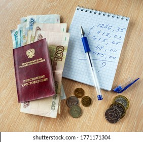 Ruble denominations are under the pension certificate of the Russian Federation. On the table is a notebook with calculations, a pen and coins. - Shutterstock ID 1771171304