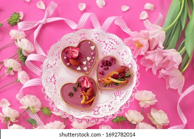 Ruby chocolate mendiant on pink plate with tulip and rose flowers.Valentines or mothers day background.