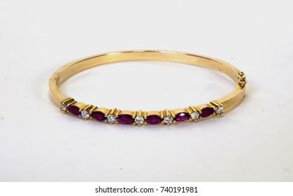 Ruby and diamond gold bracelet on a white background.