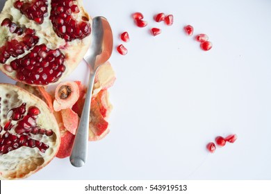 ruby pomegranate seeds and spoon on white background