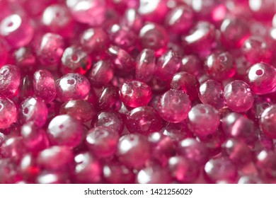 Ruby stones lie on a white table, a white background. Natural stones ruby, ruby beads. Pink ruby background.