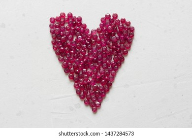 Ruby stones lie on a white table in the shape of a heart. Natural stones ruby, ruby beads. Pink heart of ruby.