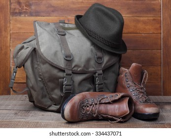 Rucksack with old boots and hat on wooden background.