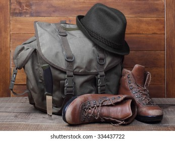 Rucksack with old boots, knife and hat on wooden background. Traveller concept