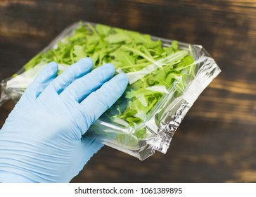 Rucola salad in a package in a hand in a rubber glove.