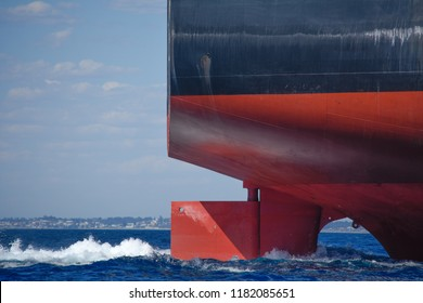 The rudder of a large ship steers it on a steady course