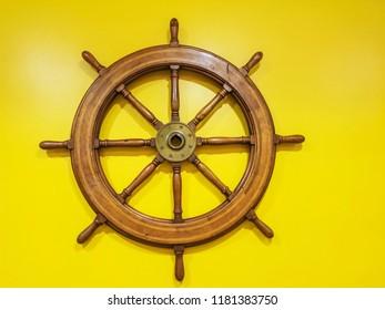 Rudder wheel in yellow background