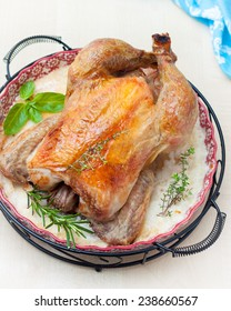 ruddy baked chicken on a platter with herbs