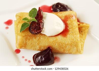 Ruddy pancake with plum jam and sour cream