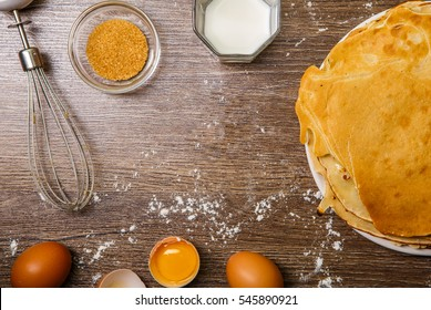 Ruddy pancakes on plate on wooden background with flour, eggs, milk, cane sugar