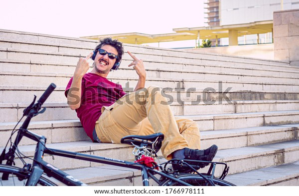 rude and arrogant young man showing the middle finger of both hands, poses next to his bike, concept of urban mobility and street lifestyle