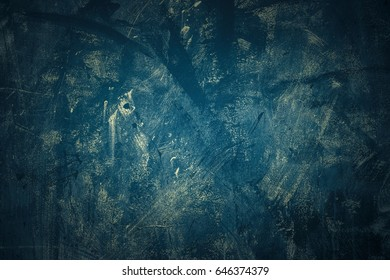 Rude background of Navi color in grunge style. Uneven painting with traces of scratches. Background or texture.