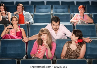 Rude bearded man talking to ladies in a theater