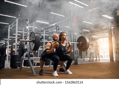 Rude brutal trainer with bald head and thick brunette beard standing behind young female powerlifter, backing her up, controlling process of squatting using heavy barbell in gym, white smoke in air