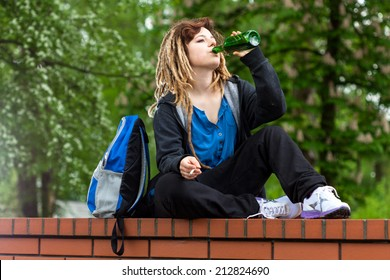 Rude girl playing hookey and drinking alcohol outdoors