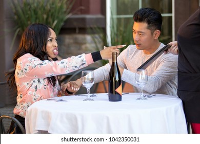 Rude girlfriend complaining to a waitress in a restaurant with an embarrassed boyfriend trying to calm her down.  The image depicts service in the food industry and angry customers.