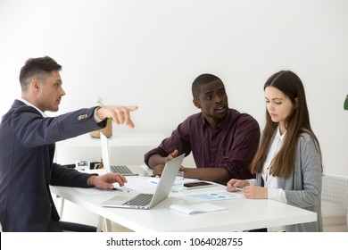 Rude multiracial businessmen humiliating, offending or firing upset frustrated businesswoman colleague telling to leave group meeting, harassment, sexism and gender discrimination at work concept