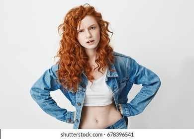 Rude young girl with red curly hair looking at camera brutally with arms akimbo over white background.