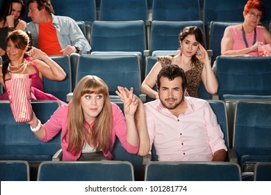Rude young woman with man in theater audience
